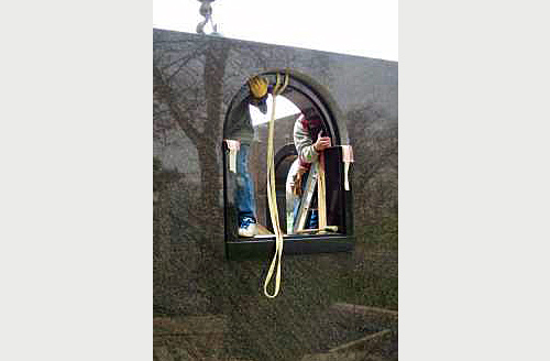 Peter Troost Monument Company craftsmen install a custom arched granite window frame in the private family mausoleum.